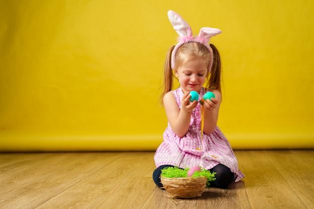 Ragazza felice bionda del bambino con le orecchie del coniglietto e canestro delle uova per pasqua