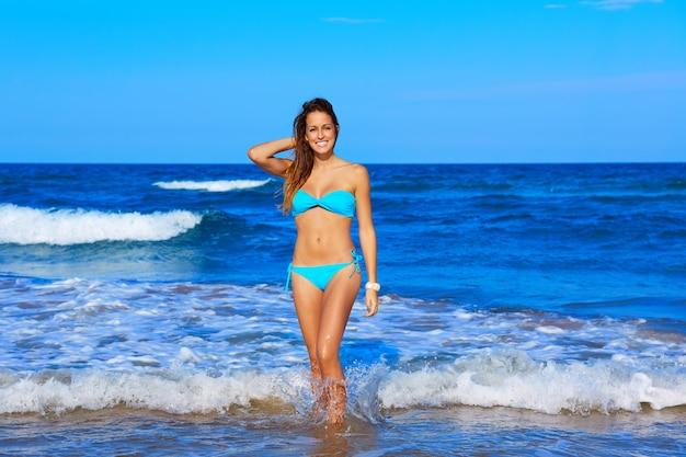 Ragazza felice castana che cammina nella riva della spiaggia