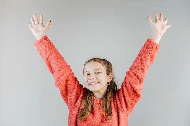 Ragazza felice che alza le sue braccia su sfondo grigio