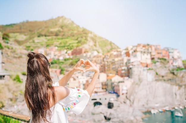 Ragazza felice che fa con le mani a forma di cuore sul vecchio villaggio costiero nel parco nazionale delle cinque terre.