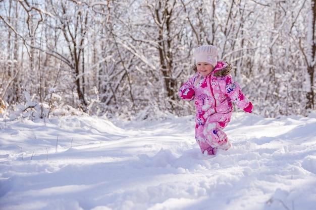 Ragazza felice che funziona nella neve
