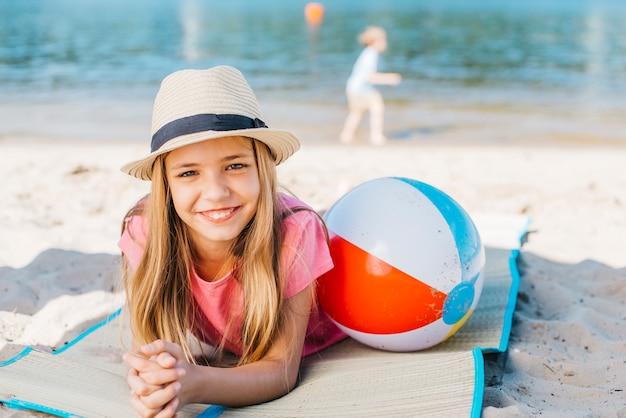 Ragazza felice che ghigna con la palla alla spiaggia