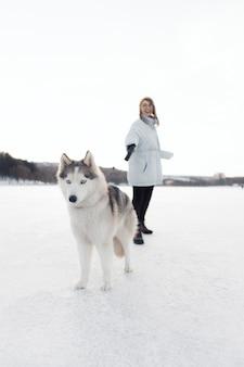 Ragazza felice che gioca con il cane del husky siberiano nel parco di inverno