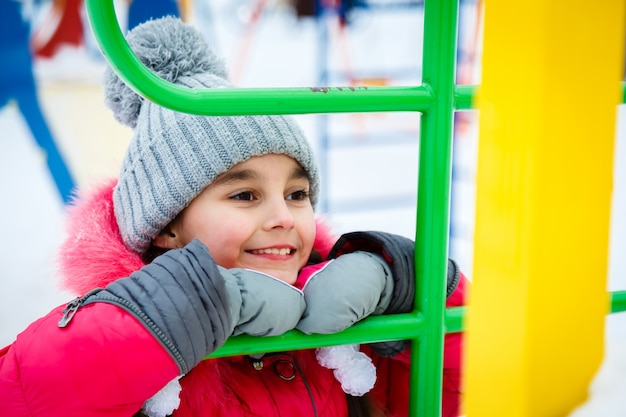 Ragazza felice che gioca in un parco giochi al giorno gelido di inverno.