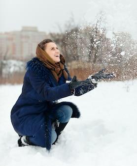 Ragazza felice che lancia i fiocchi di neve