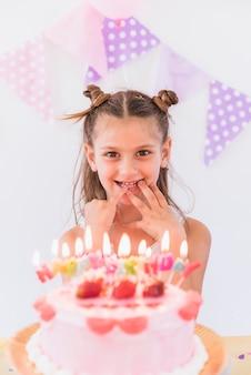 Ragazza felice che mette le sue dita in bocca in piedi dietro la torta di compleanno