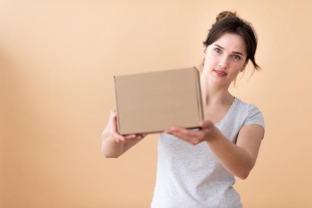 Ragazza felice che mostra la scatola del mestiere in sue mani e che sorride allegro nello spazio. casella a fuoco con spazio libero per il testo.