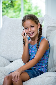 Ragazza felice che parla sul telefono cellulare mentre sedendosi sul sofà
