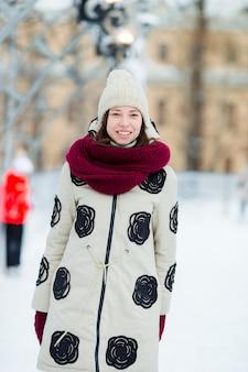 Ragazza felice che pattina sulla pista di pattinaggio sul ghiaccio all'aperto