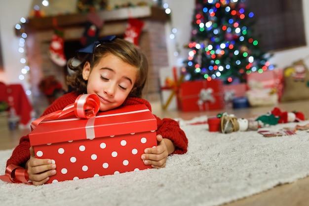 Ragazza felice che pone su un regalo