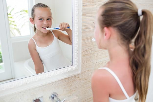 Ragazza felice che pulisce i suoi denti in bagno
