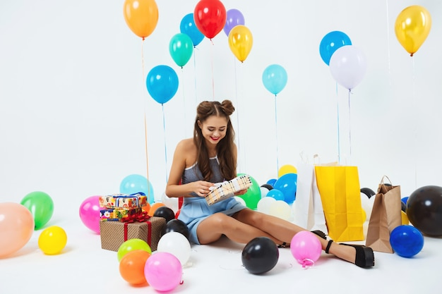 Ragazza felice che scopre le scatole del regalo di compleanno che si siedono con i palloni dell'elio