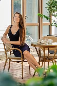 Ragazza felice che si distende su una sedia di vimini nel cortile