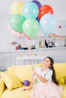 Ragazza felice che si siede sul sofà che tiene i palloni variopinti
