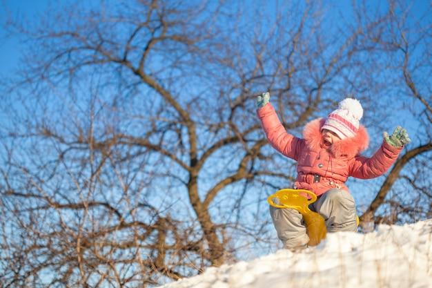 Ragazza felice che sledding all'aperto il chiaro giorno di inverno