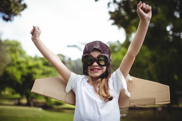 Ragazza felice che sta nel parco con le mani sollevate