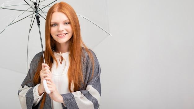 Ragazza felice che tiene ombrello trasparente