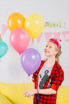 Ragazza felice che tiene palloncini colorati