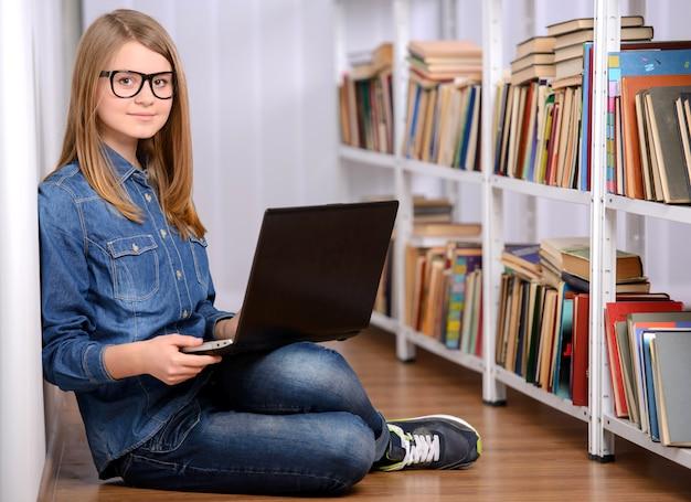 Ragazza felice che utilizza un computer portatile nella grande biblioteca.