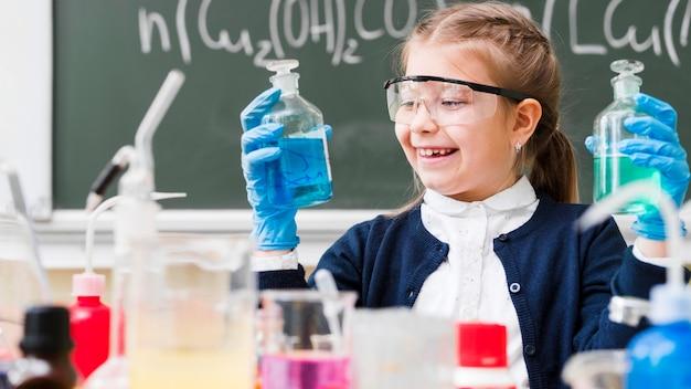 Ragazza felice con gli occhiali di protezione che tengono le boccette