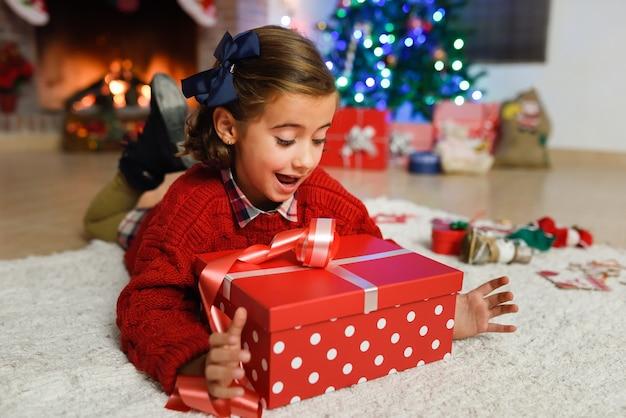 Ragazza felice con gli ornamenti di natale ed il regalo