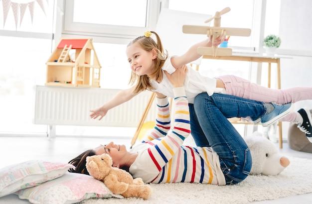 Ragazza felice con il gioco grazioso della madre