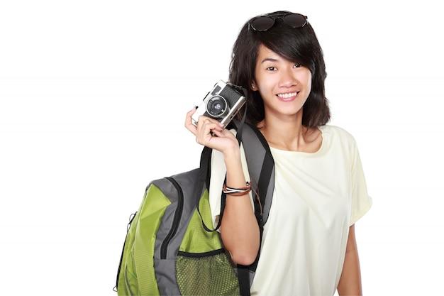 Ragazza felice con la macchina fotografica d'annata che va in vacanza