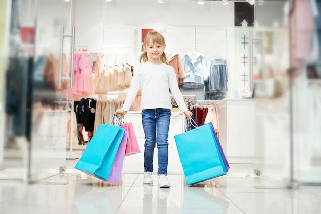 Ragazza felice con molti sacchetti della spesa variopinti nel deposito.