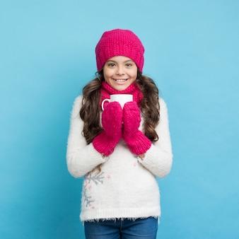 Ragazza felice con sorridere dei vestiti di inverno