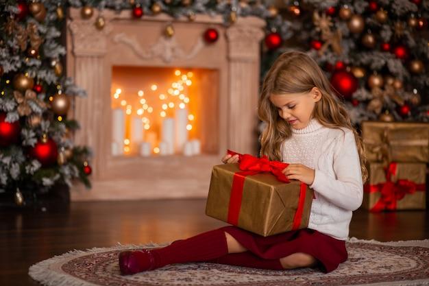 Ragazza felice con un regalo di capodanno in mano su uno sfondo di un camino e albero di natale nelle luci