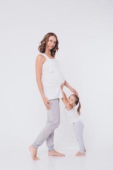 Ragazza felice del bambino che abbraccia la pancia della madre incinta, la gravidanza e il nuovo concetto di vita
