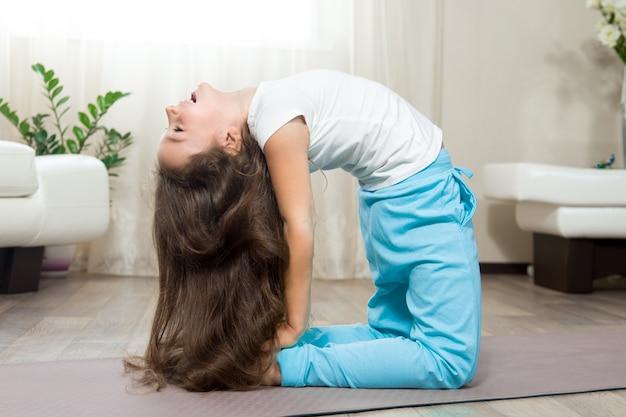 Ragazza felice del bambino che fa yoga a casa