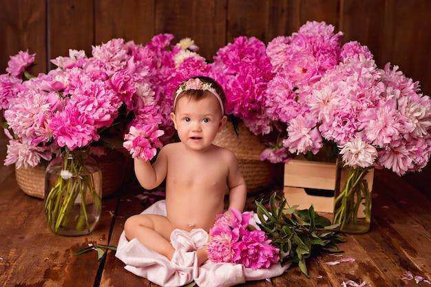 Ragazza felice del bambino che si siede in asciugamano dopo il bagno e la stazione termale. mazzi di peonie rosa.