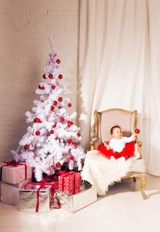 Ragazza felice del bambino del bambino vicino ad un albero di natale