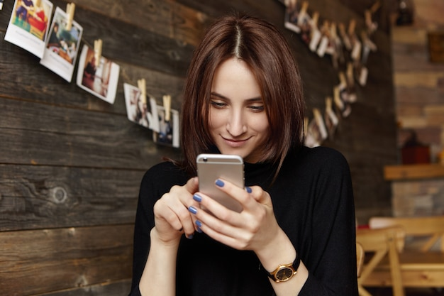 Ragazza felice del brunette in vestiti neri facendo uso della connessione di internet senza fili libera sullo smartphone mentre riposando al ristorante con l'interno accogliente e le immagini che appendono sulla parete di legno