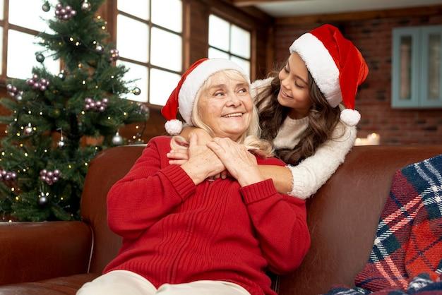 Ragazza felice del colpo medio che esamina sua nonna