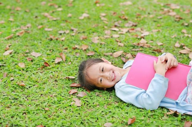 Ragazza felice del piccolo bambino con il libro che si trova sull'erba verde con le foglie secche nel giardino di estate.
