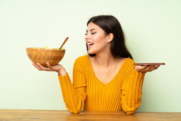 Ragazza felice dell'adolescente con insalata e cioccolato