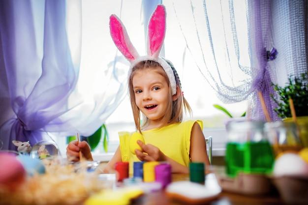 Ragazza felice di pasqua in orecchie del coniglietto che dipingono le uova, piccolo bambino a casa. vacanze di primavera