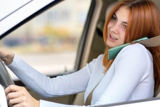 Ragazza felice di redhead che parla sul suo telefono cellulare al volante che guida un'automobile.