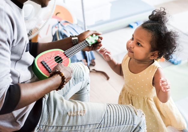 Ragazza felice e insegnante divertendosi in scuola materna