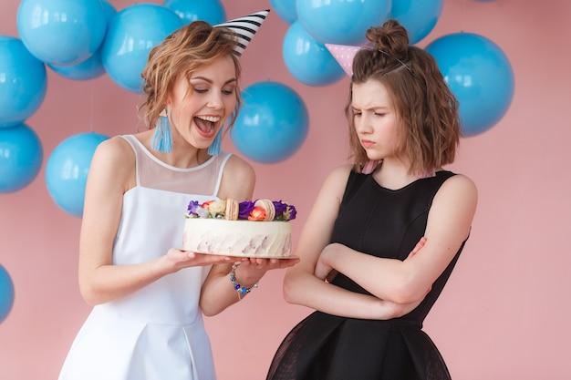 Ragazza felice e ragazza triste che guardano alla torta di compleanno. concetto di dualità