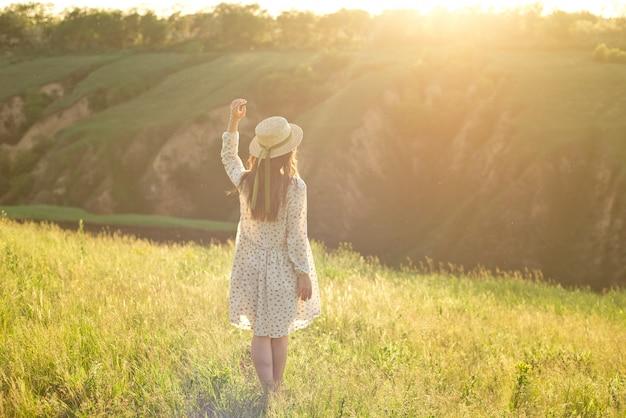 Ragazza felice giovane studente in abito estivo e cappello di paglia nelle mani. camminare all'aperto al parco.