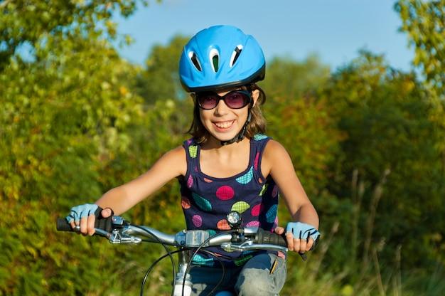 Ragazza felice in bicicletta all'aperto. bambino sorridente in bicicletta