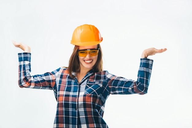 Ragazza felice in camicia blu e rossa, occhiali e casco protettivo arancione