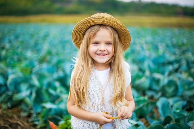 Ragazza felice in cappello di paglia sul campo di cavoli
