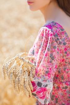 Ragazza felice in cappello sul campo di grano. cappello grande e capelli lunghi