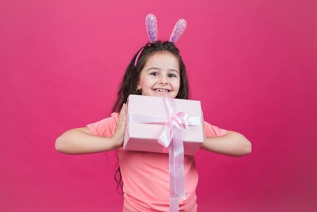 Ragazza felice in orecchie da coniglio con scatola regalo
