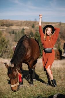 Ragazza felice in un cappello nero con un cavallo