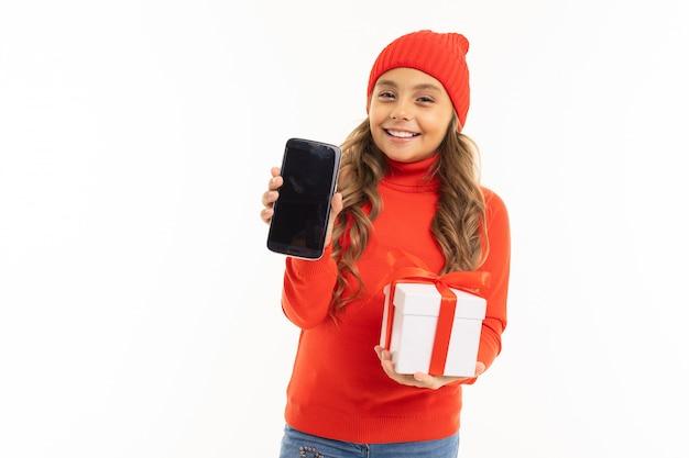 Ragazza felice in un cappello rosso con un regalo con un ribbond rosso un telefono in mani su bianco